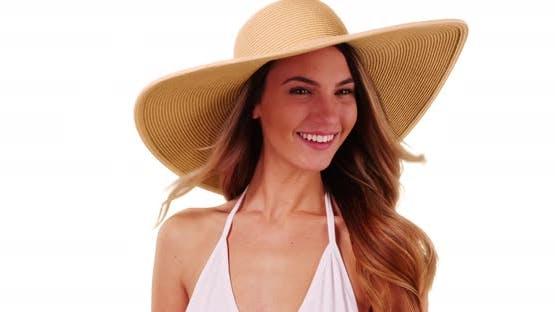Close up of attractive female in bikini modeling floppy sunhat in studio