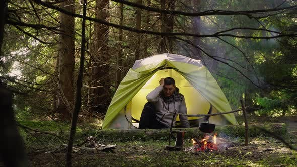 A Man in a Tent in the Forest