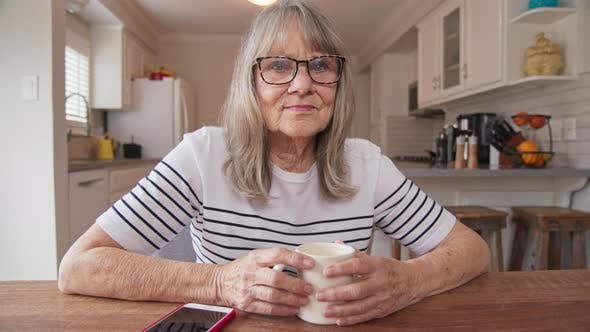 Thumbnail for Senior woman looking at camera with her morning coffee at kitchen table