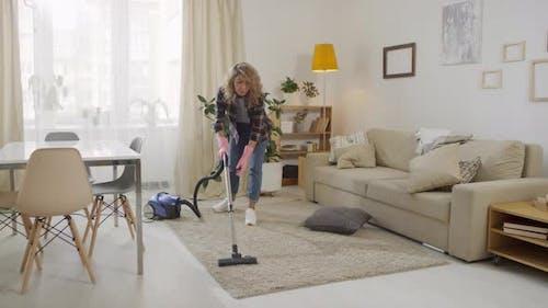 Young Woman Vacuuming at Home