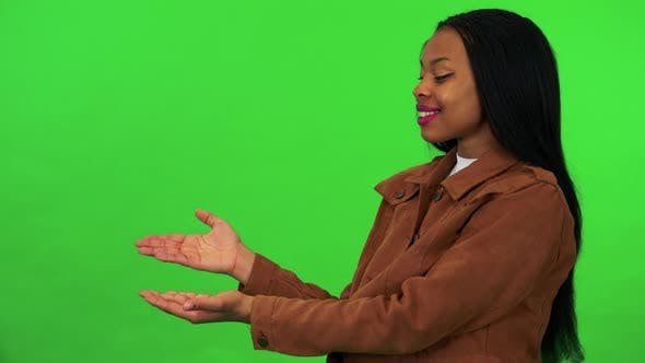 A Young Black Woman Presents Something - Green Screen Studio