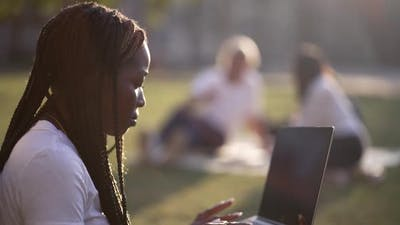 Multiracial Mates Using Laptops Studying in Nature