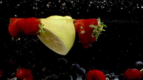 Thumbnail for Several blueberries falling over a lemon, immersed in water with some strawberries and cherries