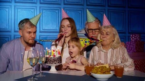 Mädchen feiert Geburtstagsfeier mit Eltern Senior Großeltern Familie bläst Kerzen auf Kuchen