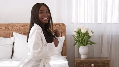 Black Woman Brushing Smooth Straight Hair Sitting In Bedroom Indoor