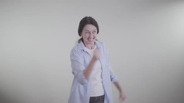 Thumbnail for Excited Caucasian Woman Making Victory Gesture, Spinning and Dancing on White Background. Portrait