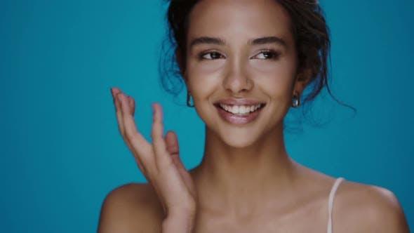 Thumbnail for ziemlich Mädchen berühren Ihr Wangen und spielerisch lächelnd zu Kamera isoliert auf blau