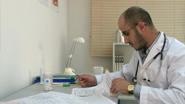 Thumbnail for Busy Male Physician Working with Papers and Having Phone Conversation in His Office