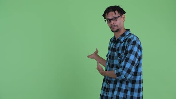 Thumbnail for Happy Young African Hipster Man Talking and Showing To Back