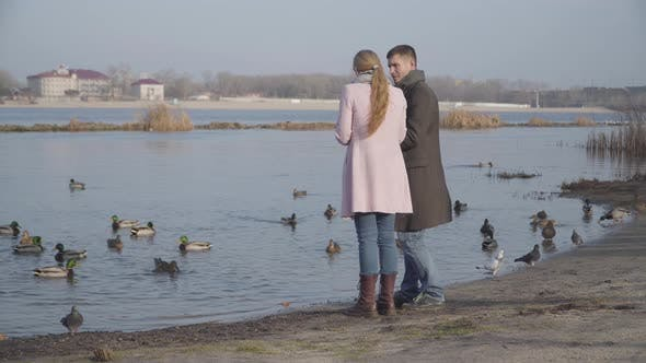 Thumbnail for Positive Caucasian Couple with Age Difference Feeding Ducks in City Park. Younger Man and Older