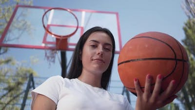 Portrait Adorable Teen Brunette Girl Holding a Basketball Ball Looking at the Camera Standing