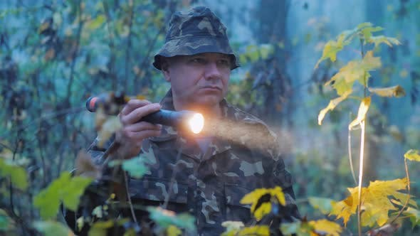 Thumbnail for A Man Shines a Flashlight at Dusk in the Forest. Search Operation