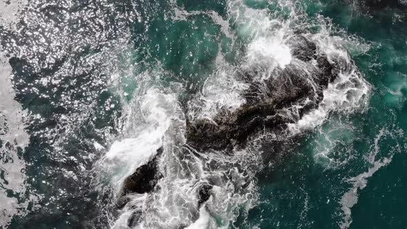 Top Aerial View of Ocean Waves Splash Against Rocks Background