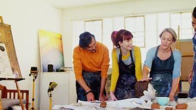 Drawing teacher assisting artists on ceramic sculpture