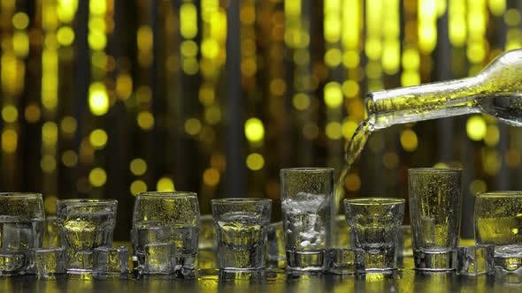 Thumbnail for Barman Pour Frozen Vodka From Bottle Into Shot Glass. Ice Cubes Against Shiny Gold Party Background