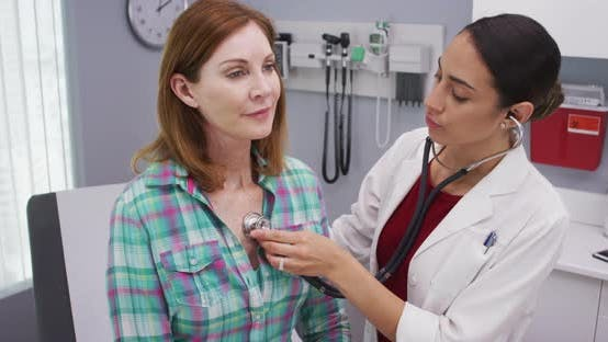 Thumbnail for Lovely young latina doctor using stethoscope to examine senior patients vitals