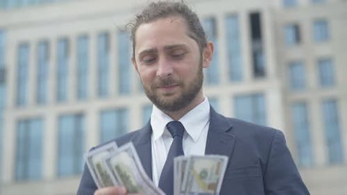 Portrait of Handsome Successful Businessman Counting Pack of Money Outdoors. Happy Confident