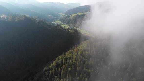 Flying Through the Clouds Over Carpathian Mountain Valley with Village in Summer