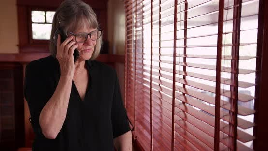 Lovely senior lady talking on smartphone with friend inside home by window