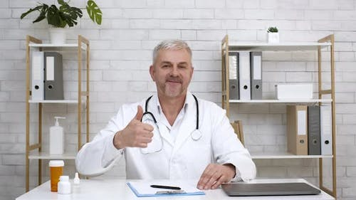 Male Doctor Gesturing Thumbs Up Sitting In Office