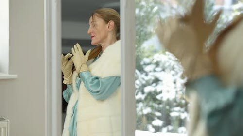 Reflection in Mirror of Stylish Confident Satisfied Wealthy Woman Putting on Ring on Glove