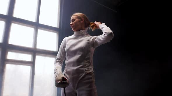 Thumbnail for A Young Woman Fencer Standing in the Studio - Lets Her Hair Down From the Bun