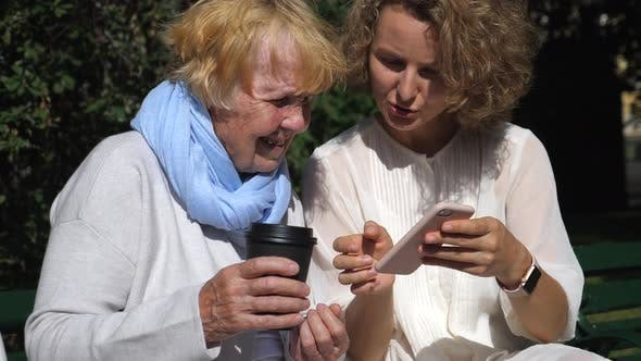People And Technology Concept. Grandmother And Granddaughter Using Smartphone