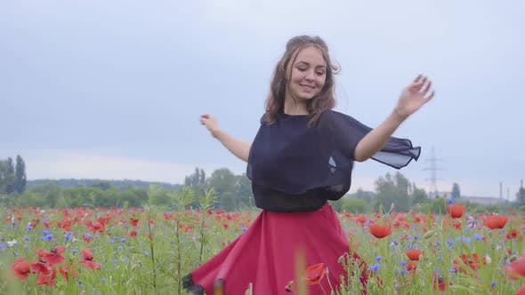 Thumbnail for Cute Young Girl Running and Dancing in a Poppy Field Smiling Happily