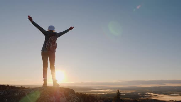 Thumbnail for Crane Shot of A Successful Woman Traveler at the Top of the Mountain Raises Her Hands Up. Reach the
