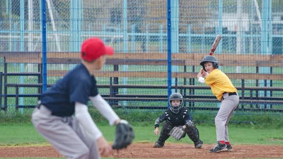 Boys Play Baseball at School, the Pitcher Throws the Ball Toward a Batter, the Catcher Catches a