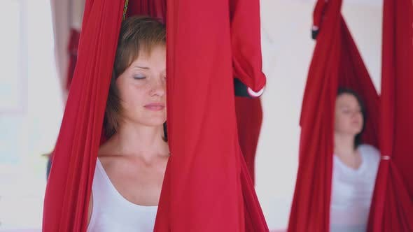 Nice Young Woman Sits with Closed Eyes in Fly Yoga Hammock