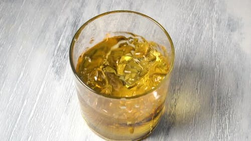 Falling ice cube into a glass of whiskey