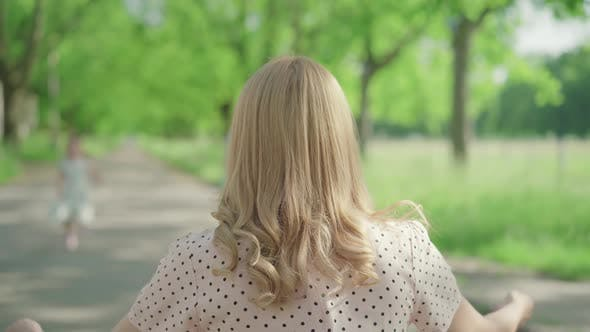 Thumbnail for Back View of Blond Caucasian Woman Sitting on Alley in Summer Park As Children Running To Her