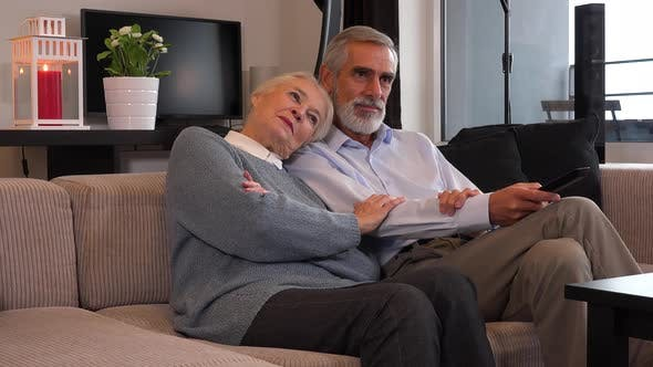 Thumbnail for An Elderly Couple Sits in A Living Room in An Apartment and Watches Tv