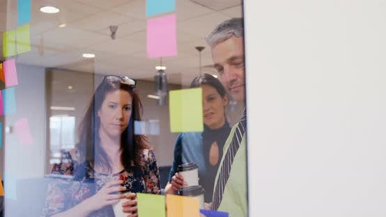 Thumbnail for Business people discussing over sticky notes in a modern office 4k