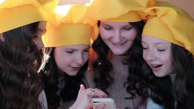 Children in yellow hats use a smartphone in the kitchen