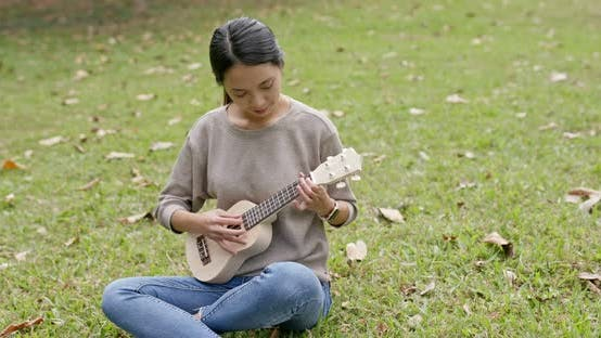 Asian Woman enjoy play ukulele and song in the park