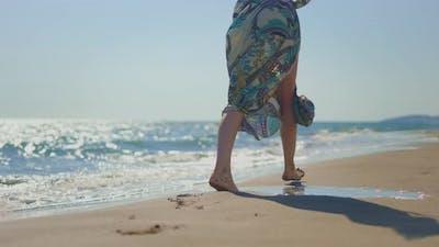 Woman legs walking in wet sand