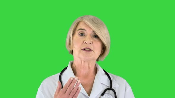 Pleasant Carrying Doctor Lady Talking To Camera on a Green Screen Chroma Key