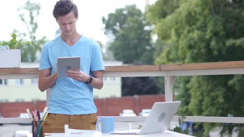 Sunny Day, Man Standing and Browsing on Tablet in Balcony, Gadget