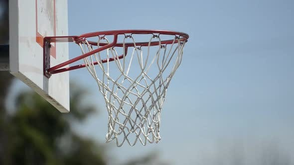 Thumbnail for Extreme closeup of a man slam dunking a basketball on a playground court.