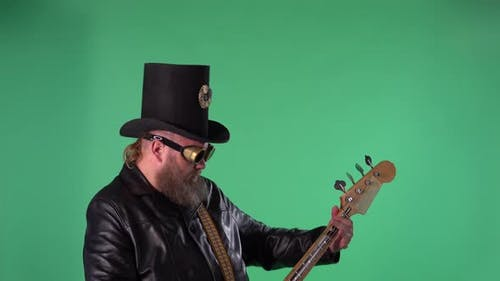 Bearded Man in Long Leather Coat an Irish Style Hat and Original Glasses Plays the Red Guitar