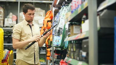 Man Customer Choosing Fishing Rods in the Store for Fishing