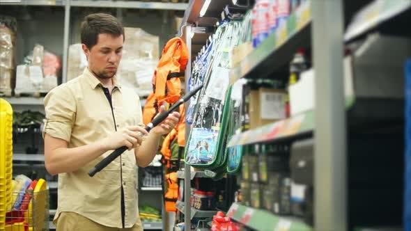Man Customer Choosing Fishing Rods in the Store for Fishing