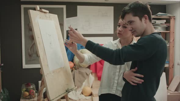 Thumbnail for Female Painter Teaching Young Man How To Draw Classical Face
