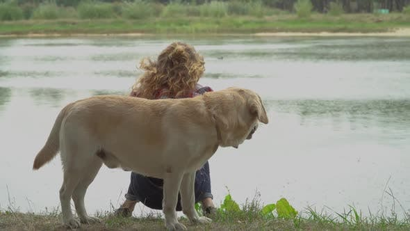 Thumbnail for Redhead Woman and Labrador Is Resting Near the Water