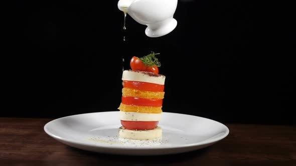 Thumbnail for Gießen Sie Olivenöl auf Mozzarella Salat in Zeitlupe. Footage auf schwarzem Hintergrund.  Italienisch