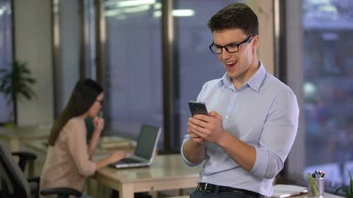 Young Man Using Smart Home App on Smartphone While in Office, Modern Technology