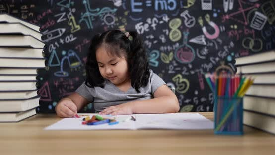 Lovely girl enjoy to drawing on paper in classroom