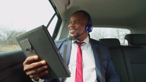 Positive Businessman Enjoying Music in Headphones in Vehicle